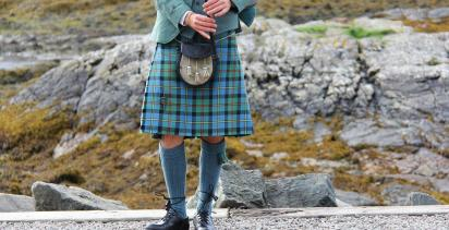 lower body of man in Highlander dress and kilt playing the bagpipes